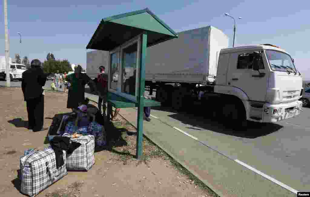 A Russian convoy carrying humanitarian aid for Ukraine drives to the Russia-Ukraine border crossing point while Ukraine refugees stand nearby, in Rostov region, Russia, Aug. 22, 2014.