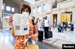 "Seorang perempuan menunjukkan ""Green Pass"" COVID-19-nya di stasiun kereta di Milan, Italia, 1 September 2021. (REUTERS/Flavio Lo Scalzo)"