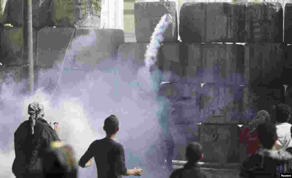 A protester opposing Egyptian President Mohamed Morsi throws a tear gas canister, earlier thrown by riot police near Tahrir Square, Cairo, Egypt, January 25, 2013.