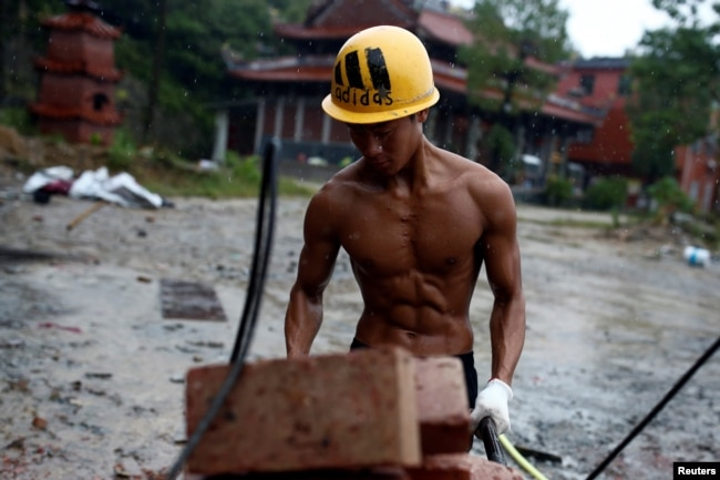 file shi shenwei pulls a wheelbarrow at the construction site of a buddhist temple in