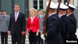 German Defense Minister Ursual von der Leyen, center, and her U.S. counterpart Ash Carter, left, inspect an honor guard during a welcome ceremony at the Defense Ministry in Berlin, Germany, June 22, 2015.
