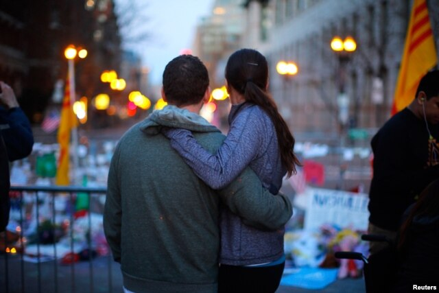 A couple embraces at a memorial on Boylston Street to the bombing victims, April 21, 2013.