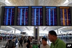 香港航空業數以千計的職工響應罷工,機場大堂的顯示屏顯示航班取消。