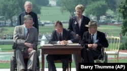 FILE - In this July 26, 1990 file photo, President George H. W. Bush signs the Americans with Disabilities Act during a ceremony on the South Lawn of the White House.