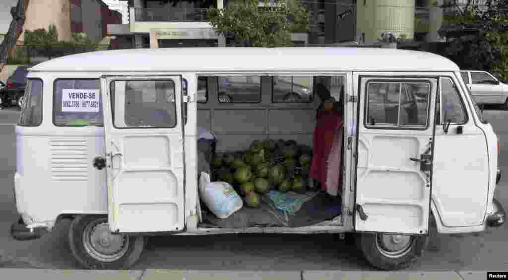 In a beachside parking area, a van contains a stockpile of coconuts, in Recife, June 11, 2014.