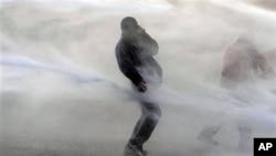 星期四在布魯塞爾歐盟總部外邊﹐比利時警方使用高壓水槍驅散示威者