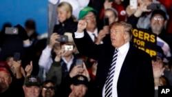 Prezidan Donald Trump Kap Voye Men Bay yon foul Patizan li Jedi premye Novanm Nan Eta Missouri. AP/ Charlie Riedel.