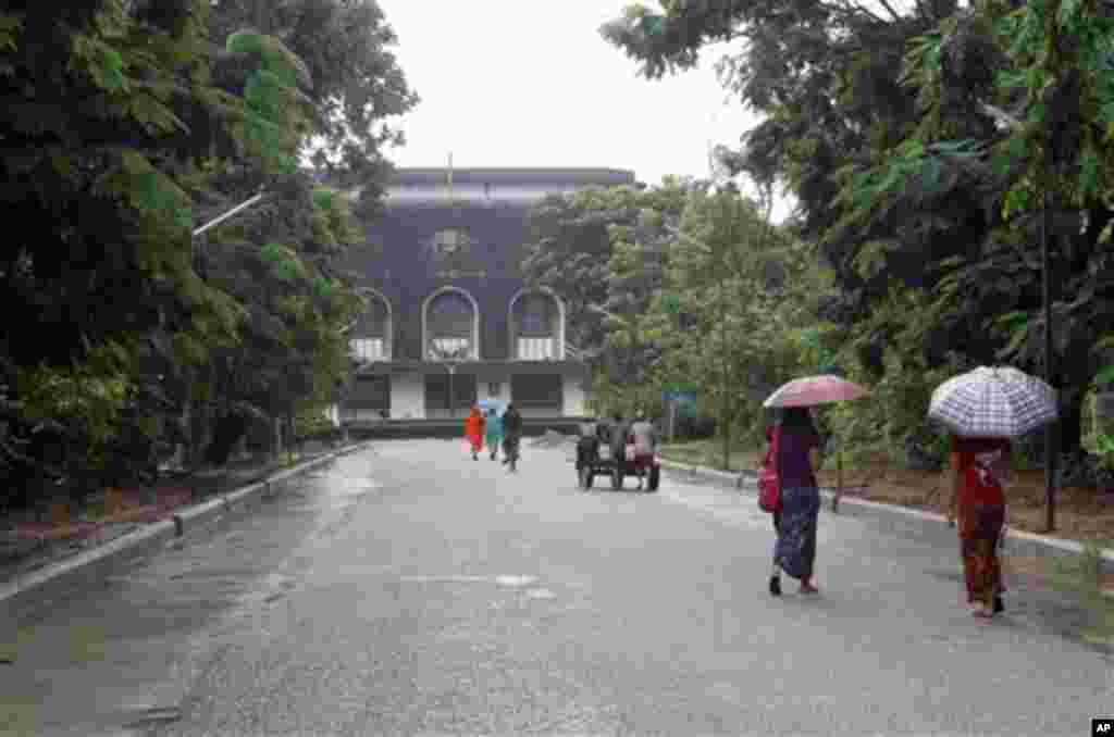 People walk on a road leading to the convocation hall of Yangon University in Yangon, Myanmar Thursday, June 28, 2012. The university was once one of Asia's finest and a poignant symbol of an education system crippled by Myanmar's half a century of milita