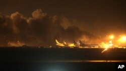 El fuego ilumina el cielo sobre el Aeropuerto Internacional Jinnah en Karachi, atacado por militantes talibanes.