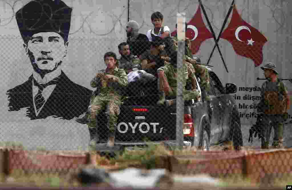 ترکیه را در حمله به شمال سوریه، گروهی از نیروهای سوری همراهی می کنند. در زمینه این عکس، تصویری از مصطفی کمال آتاترک بنیانگذار جمهوری ترکیه نیز دیده می شود.