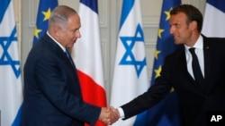 以色列总理内塔尼亚胡(左)和法国总统马克龙2018年6月5号在巴黎爱丽舍宫举行联合记者会前握手