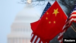 FILE - The People's Republic of China flag and the U.S. Stars and Stripes fly along Pennsylvania Avenue near the U.S. Capitol in Washington during Chinese President Hu Jintao's state visit, Jan. 18, 2011.