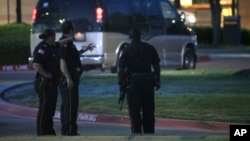 Офицеры полиции патрулируют автомобильную стоянку недалеко от здания, где в воскресенье проходила выставка карикатур на пророка Мохаммеда. Гарленд, штат Техас. США. 3 мая 2015 г.