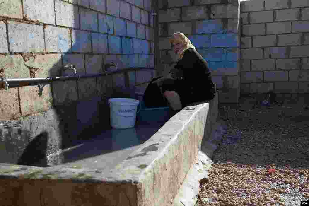 A woman washes clothes in the Za'tari refugee camp. (Y. Weeks/VOA)