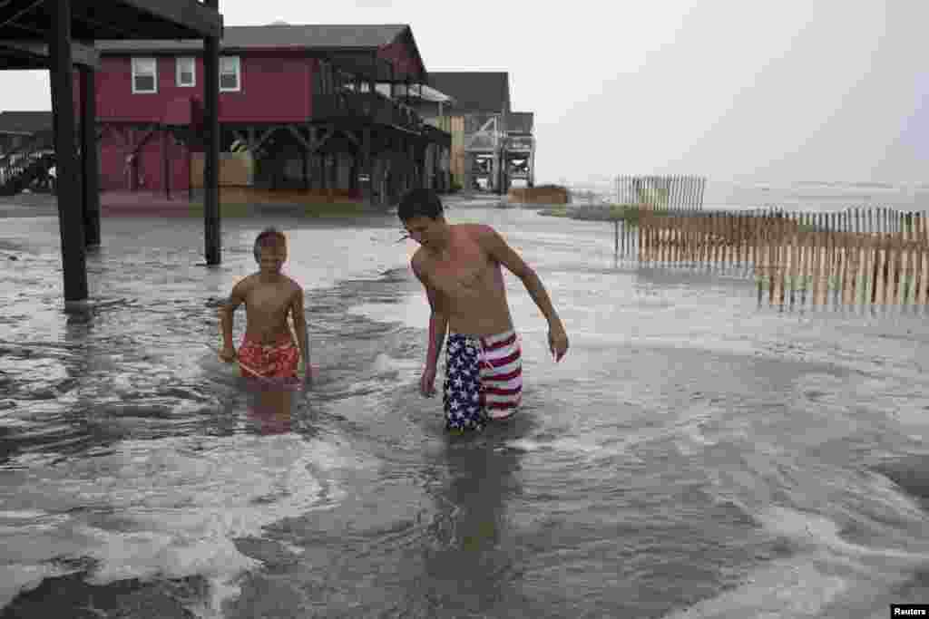 Kyler Cook, 18, (R) and Brodie Fox, 10, both from Tiffen, Ohio, walk through the storm surge of Hurricane Arthur, in Ocean Isle Beach, North Carolina, July 3, 2014