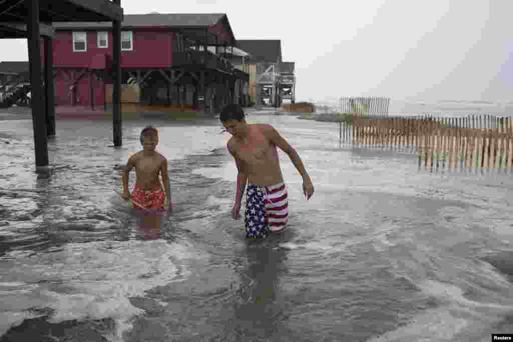 Kyler Cook, 18, (R) and Brodie Fox, 10, both from Tiffen, Ohio, walk through the storm surge of Hurricane Arthur, in Ocean Isle Beach, North Carolina, July 3, 2014