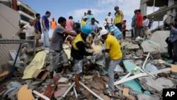 에콰도르 지진 피해 지역인 페데르날레스에서 17일 구조 요원들이 건물 잔해에 묻혀있던 시신을 수습하고 있다.