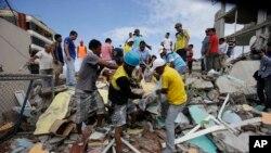 Những người tình nguyện đưa một thi thể ra khỏi một ngôi nhà bị phá hủy ở thành phố Pedernales, Ecuador, ngày 17 tháng 4, 2016.
