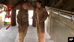 El general de Infantería de Marina Frank McKenzie, jefe del Comando Central de Estados Unidos, conversa con un oficial de la Fuerza Aérea debajo de un bombardero B-52 el viernes 7 de junio de 2019, en la base aérea de al-Udeid, en Qatar.