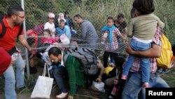 Para migran Timur Tengah menerobos pagar pembatas di Horgos, Serbia untuk memasuki kota Roszke, Hungaria (14/9).
