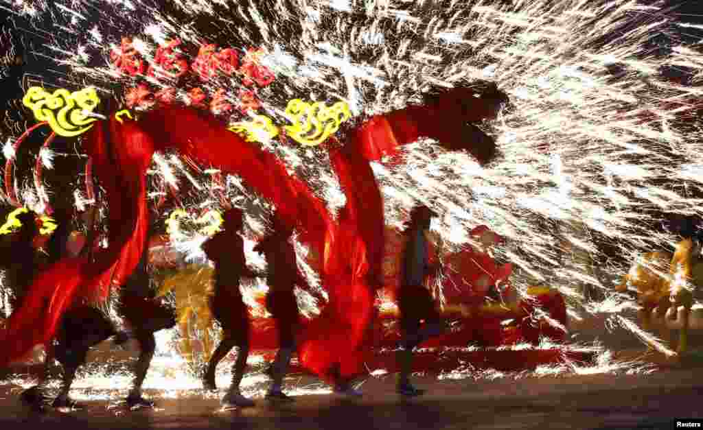 Dancers perform a fire dragon dance in the shower of molten iron spewing firework-like sparks during a folk art performance at the Happy Valley amusement park in Beijing, China, to celebrate the traditional Chinese Spring Festival on the first day of the Chinese Lunar New Year, which welcomes the Year of the Horse.