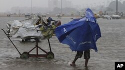A boy struggles to hold onto his umbrella during strong winds on Marina beach in the southern Indian city of Chennai, December 29, 2011.
