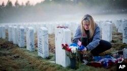 Bà Jiffy Helton Sarver đặt hoa tại mộ của con trai Joseph Helton, tử trận trong khi phục vụ tại Iraq năm 2009, tại Nghĩa trang Quốc gia Georgia ở Canton, bang Georgia, Hoa Kỳ.