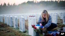 미국에서 11일 재향군인의 날인 '베터런스 데이'를 맞아, 조지아주 먼로의 지피 헬턴 새버 씨가 6년 전 이라크에서 전사한 아들의 묘에 꽃을 놓고 있다.