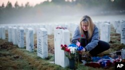 FILE - Jiffy Helton Sarver places flowers at the grave of her son, 1st Lt. Joseph Helton Jr., killed in Iraq in 2009, at Georgia National Cemetery in Canton on Veterans Day, Nov. 11, 2015. The federal government is changing how it confirms deaths.