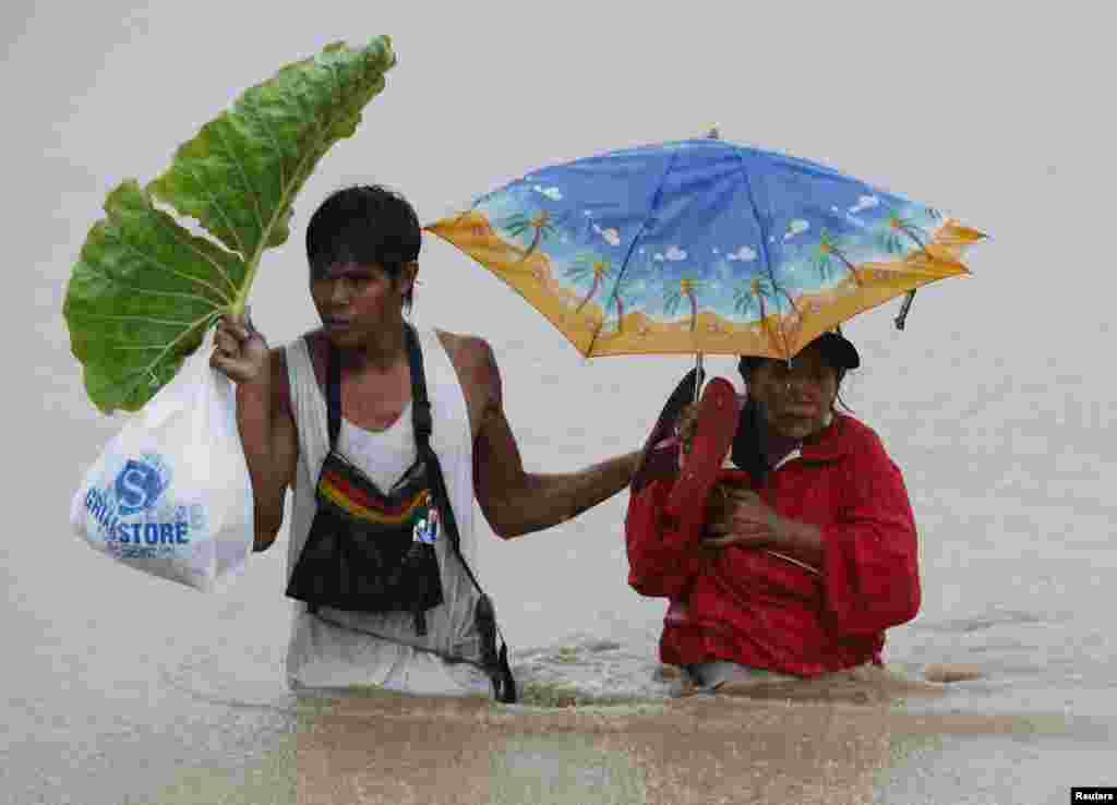 """A couple wades through floodwaters brought by tropical depression """"Agaton"""" in Kabadbaran, Agusan del Norte, in the southern Philippine island of Mindanao."""