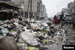 A family crosses a street piled with rubbish in Aleppo, Syria, January 5, 2013.