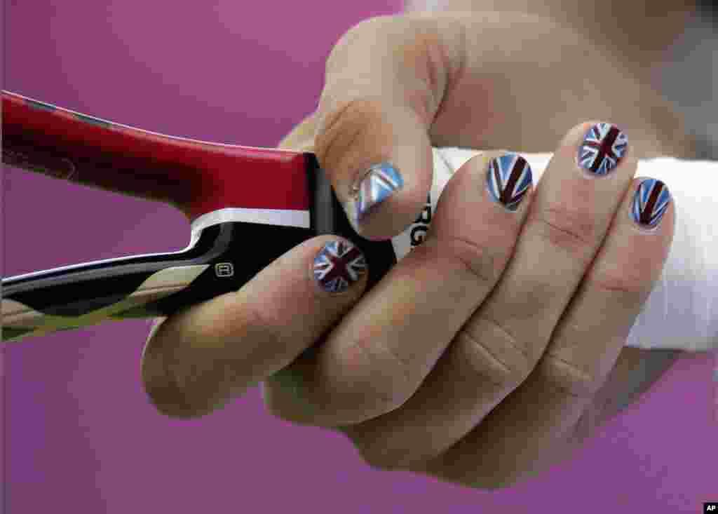 Laura Robson de Gran Bretaña muestra las uñas pintadas con la bandera británica, en el All England Lawn Tennis Club en Wimbledon,