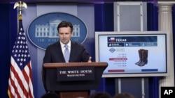 白宫发言人欧内斯特在白宫例行记者会上利用图像讨论TPP。(2015年10月13日)