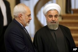 FILE - Iranian President Hassan Rouhani, right, talks with his Foreign Minister Mohammad Javad Zarif in Tehran, Iran, Nov. 24, 2015.