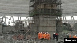 Rescue workers search the site where a power plant's cooling tower under construction collapsed, in Fengcheng, Jiangxi province, China, Nov. 24, 2016.