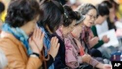 한국 대학 입학 시험인 '수능'을 하루 앞둔 11일, 서울 조계사에서 학부모들이 자녀들을 위해 기도하고 있다.