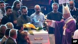 El cardenal Angelo Bagnasco bendice el ataúd del niño de nueve años, Samuel Robbiano, quien falleció en el derrumbe del puente.