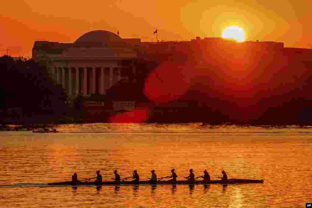 Rowers skim along the Potomac River as the sun rises over the Jefferson Memorial in Washington.