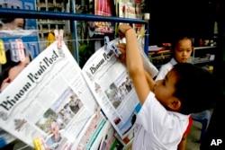 រូបឯកសារ៖ ក្មេងប្រុសម្នាក់ព្យួរកាសែតភាសាអង់គ្លេសភ្នំពេញបុស្តិ៍ (Phnom Penh Post) នៅតូបកាសែតមួយក្នុងក្រុងភ្នំពេញកាលពីថ្ងៃអង្គារទី៨ ខែមករា ឆ្នាំ២០០៨។