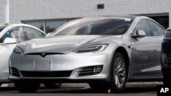This July 8, 2018, file photo shows Tesla 2018 Model 3 sedans sitting on display outside a Tesla showroom in Littleton, Colo. (AP Photo/David Zalubowsi, File)