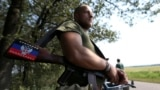 A pro-Russian separatist rebel guards a checkpoint near the village of Rozsypne in Ukraine's eastern Donetsk region August 4, 2014.