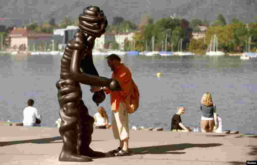 A man stands beside a sculpture of the group 'Vier Grosse Geister' (Four Big Ghosts') from 2003 by German artist Thomas Schuette on the shore of Lake Zurich in Zurich, Switzerland.
