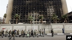 FILE - Army soldiers march in front of the burned-out headquarters of the National Democratic Party in Cairo, Feb. 15, 2011.