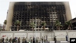 Army soldiers march in front of the burned down building of former President Hosni Mubarak's National Democratic Party in Cairo, Egypt, February 15, 2011