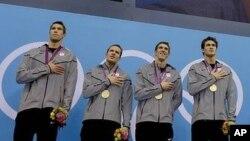 Michael Phelps (ketiga dari kiri) dan rekan setimnya berdiri di podium dalam penerimaan medali nomor 4X100 meter estafet putera (4/8).