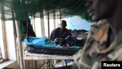 FILE - A child sick with malaria and from malnutrition lies on a bed in a hospital in Bor, South Sudan, March 15, 2014.