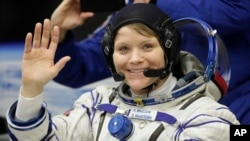U.S. astronaut Anne McClain waves before the launch of Soyuz MS-11 space ship at the Russian-leased Baikonur cosmodrome, Kazakhstan, Dec. 3, 2018.