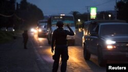 FILE - A police officer holds a flashlight during inspections at a checkpoint after 13 people were killed in battles between rival gangs in two states in central and western Mexico, Uruapan, in the state of Michoacan, Mexico, Sept. 13, 2017.