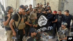 FILE - Iraqi security forces backed by Shiite and Sunni pro-government fighters celebrate as they hold a flag of the Islamic State militant group they captured in Ramadi, Anbar province, Iraq, July 26, 2015.