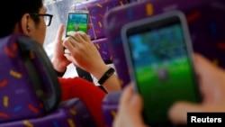 """Para penumpang main """"Pokemon Go"""" dalam bus di Hong Kong, China (12/8)."""